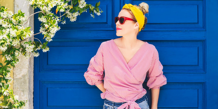 Stylish Woman standing against a blue door wearing a yellow headband and red sunglasses