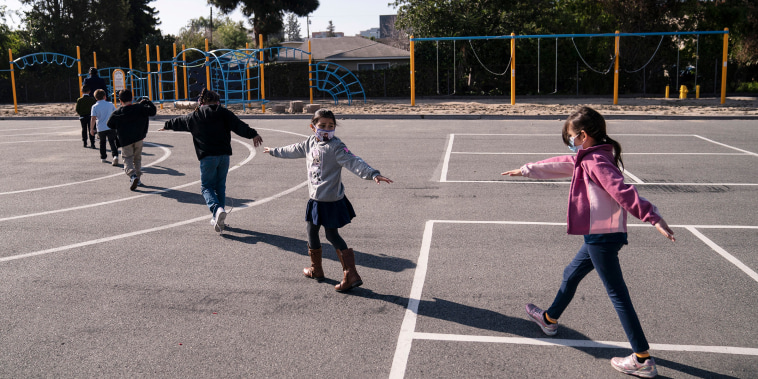 Second-grade students spread their arms for social distancing