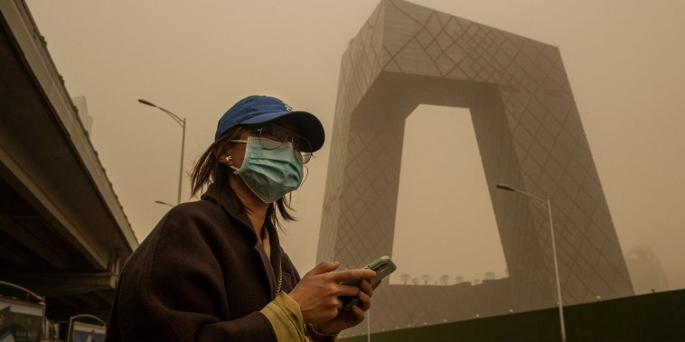 Image: A woman crosses a street during a sandstorm in the financial district in Beijing
