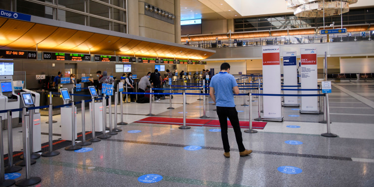 Image: Travelers check-in at Los Angeles International Airport on Feb. 4, 2021.