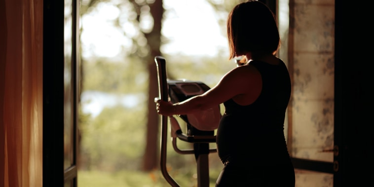 Pregnant woman looking outside her house while working out on her Elliptical