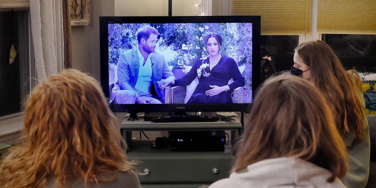 Image: People watch a televised conversation between Britain's Prince Harry with his wife Meghan Markle and U.S. host Oprah Winfrey