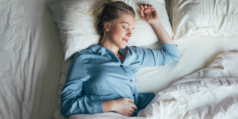 Woman fast asleep in her bed, wearing blue pajama's