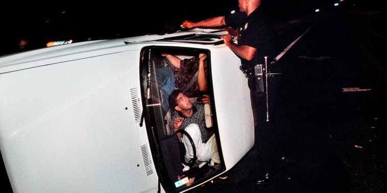 Pacific Division Officer Hoskins tries to pry open the door of a truck involved in an accident that left the driver and passenger locked in the overturned vehicle.