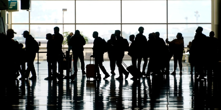Image: Travelers walk through the Salt Lake City International Airport on March 17, 2021.