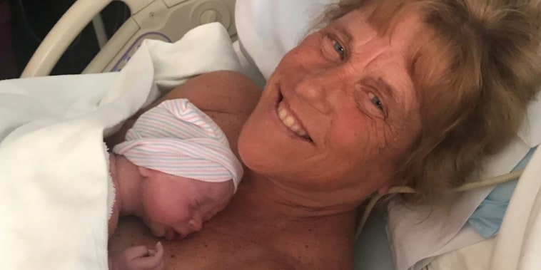 woman holds newborn in hospital bed
