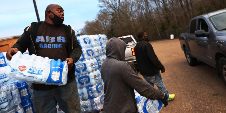 Image: Benjamin Williams and Ben Mitchell help to distribute bottled water in the parking lot of Forest Hill High School on March 5, 2021 in Jackson, Miss