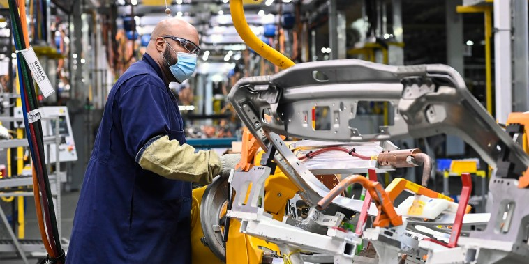 Image: GM workers use human assistance automation to weld vehicle doors at the General Motors assembly plant in Oshawa, Ontario on March 19, 2021.