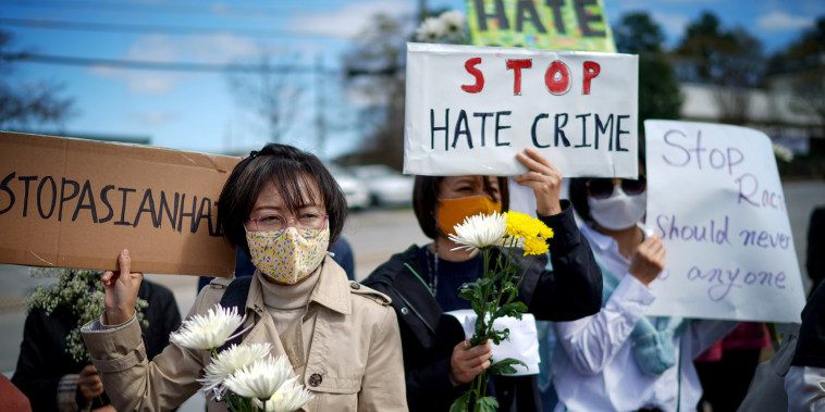 Image:  Demonstrators gather at a makeshift memorial for people who were killed in a series of attacks on three Atlanta-area spas on March 21, 2021.