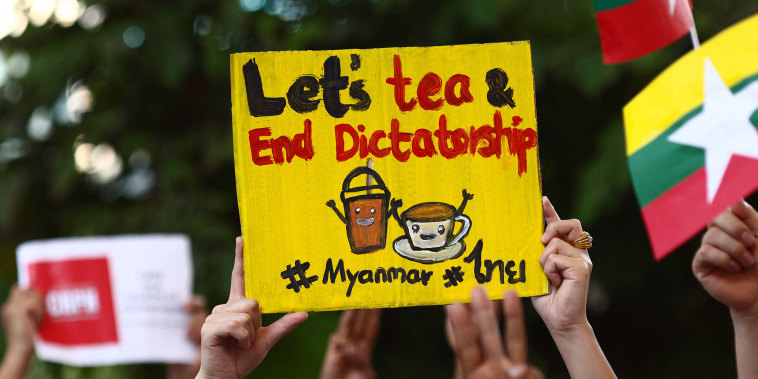 "Image: Myanmar migrants in Thailand holds signs relating to the ""Milk Tea Alliance\"" as they take part in a protest in Bangko"
