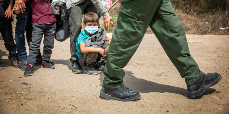 Asylum seekers await transport by U.S. Border Patrol agents on March 25, 2021 in Hidalgo, Texas.