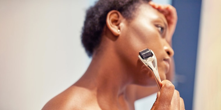 Close-up image of a woman microneedling her face with a gold and black roller