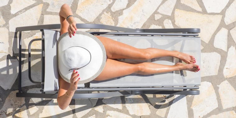 Overhead image of a woman wearing a white sun hat, laying out in the sun