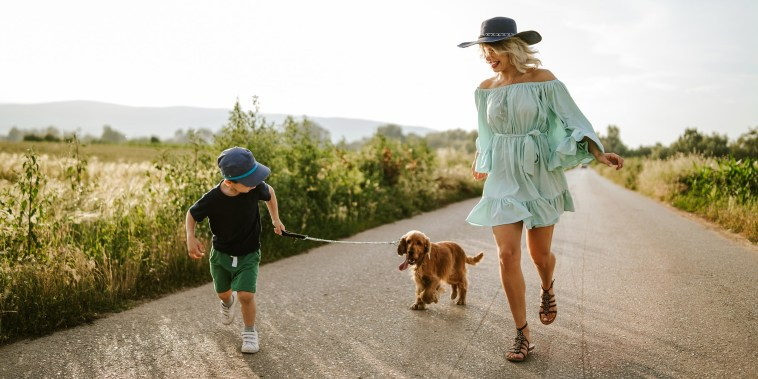 Woman in a spring mint green dress, sandals and a hat, running along side her son and puppy outside on a path