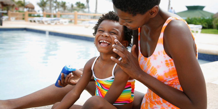 Woman applying kids sunscreen to childs face sitting by pool. The best sunscreens for kids that are dermatologist recommended. Get the best sun protection for your kids from Neutrogena, Aveeno, Baby Bum and more.