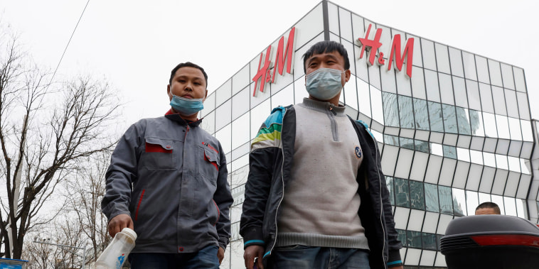 Image: Workers wearing masks pass by an H&M store in Beijing