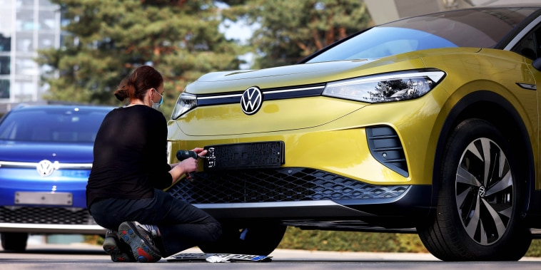 An employee prepares a new Volkswagen ID.4 SUV electric automobile for delivery  in Wolfsburg, Germany, on March 26, 2021.