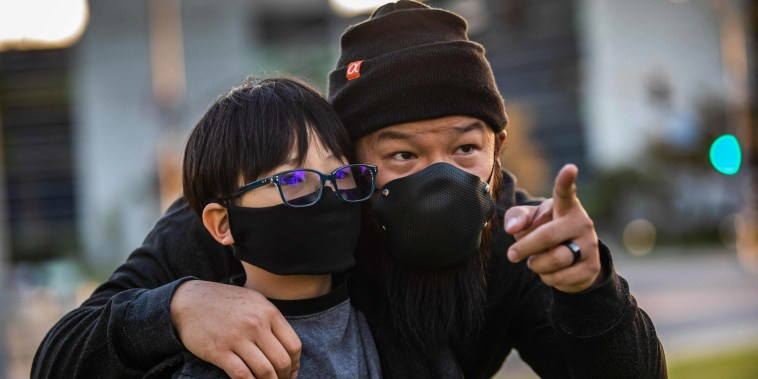 Justin Kuo and his son Zion gather with community members for a candlelight vigil in Garden Grove, Calif., on March 17, 2021, to unite against the recent spate of violence targeting Asian Americans.