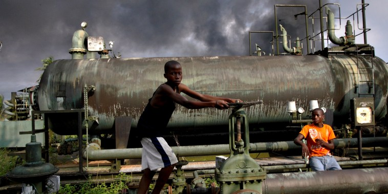 Image: Children play on an abandoned oil flow station near smoke from a burning oil pipe in Kegbara Dere, Nigeria, in 2007.