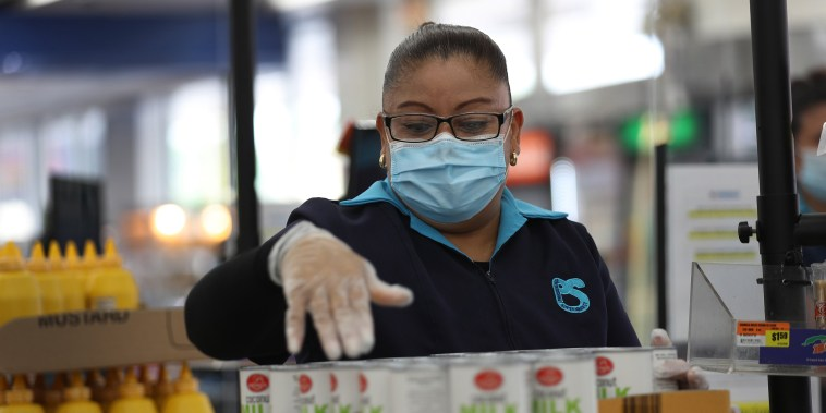Image: Lorena Martinez wears a mask and gloves as she works as a cashier