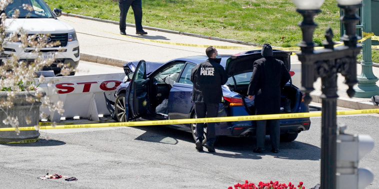 Image: U.S. Capitol Police officers stand near a car that crashed into a barrier on Capitol Hill, on April 2, 2021.