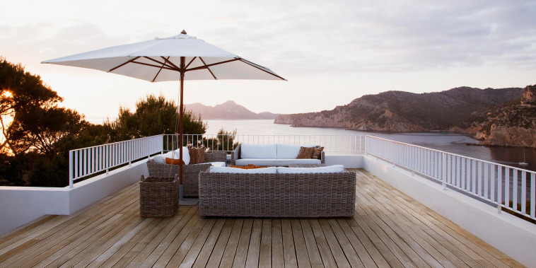 Image of patio white wicker furniture with an umbrella overlooking a beautiful ocean view