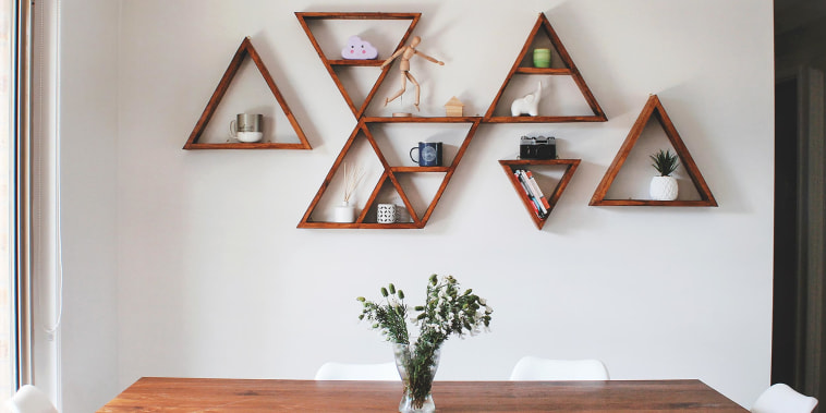 Image of dining room with a wooden table and wooden triangle wall shelves, decorating a blank white wall