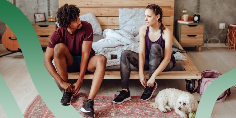 Woman and man wearing athletic clothes, sitting on their bed, putting on sneakers