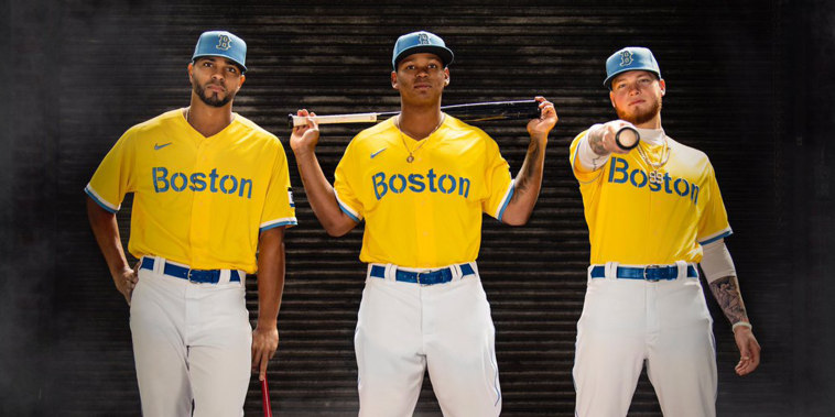 Boston Red Sox shortstop Xander Bogaerts, third baseman Rafael Devers, and outfielder Alex Verdugo pose for a portrait as they display 2021 Boston Red Sox Nike City Connect uniform.