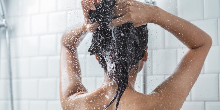 Woman washing her hair in the shower with shampoo
