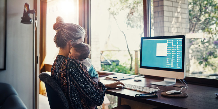 young woman working at home while holding her newborn baby son