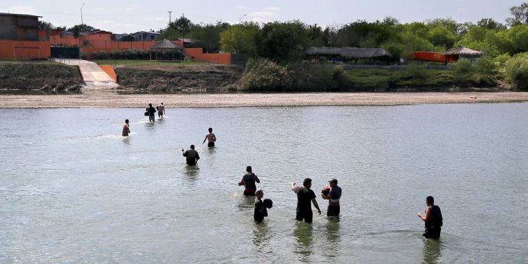 A group of undocumented immigrants wade across the Rio Grande at the U.S.-Mexico border on March 14, 2017 in Roma, Texas.