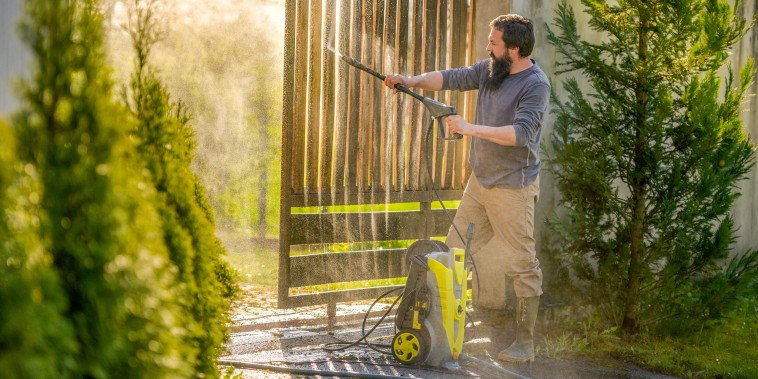 Man power washing his wooden front gate. Best pressure washers in 2021.