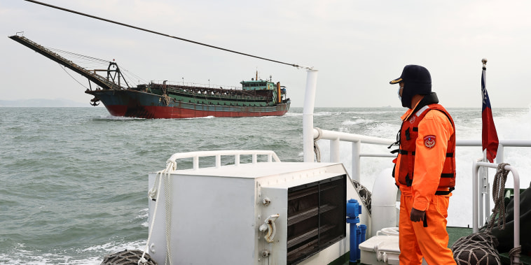 Image: A Taiwanese coast guard looks at a sand-dredging ship with a Chinese flag in the waters off the Taiwan-controlled Matsu islands, on Jan. 28, 2021.