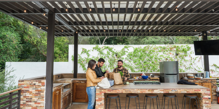 Three people standing in an outdoor backyard kitchen, covered by an overhang, with groceries