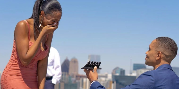 man kneels in blue suit over atlanta skyline holding five different rings to crying woman in rust orange bodycon dress