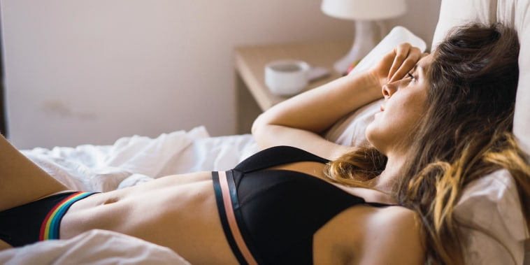 Woman laying in bed, wearing a comfy black bra