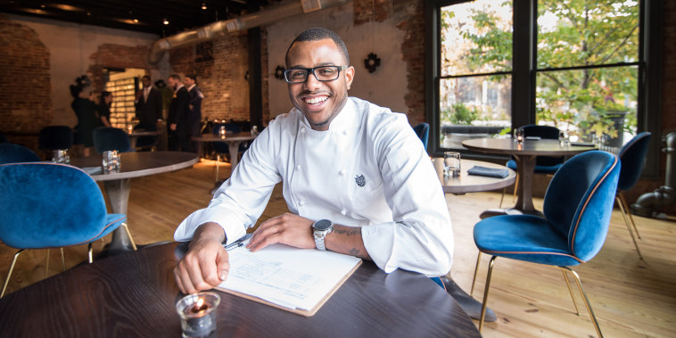 Chef Onwuachi in a white chef's jacket sits at a table in a trendy restaurant with natural light and exposed brick