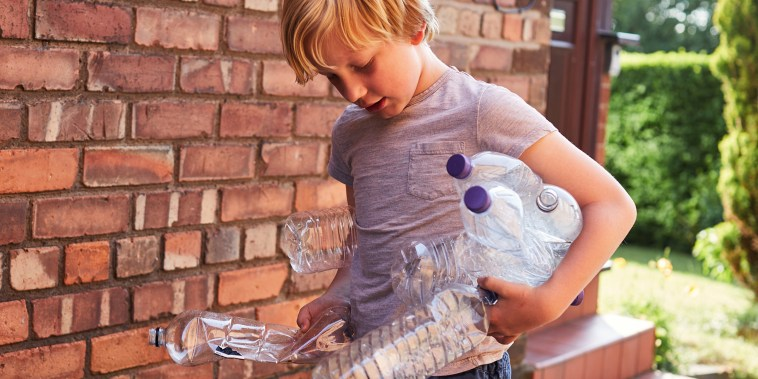 Child recycles plastic water bottles.