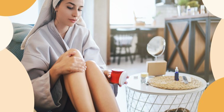 Woman wearing a robe and towel on her head, rubbing lotion on her legs