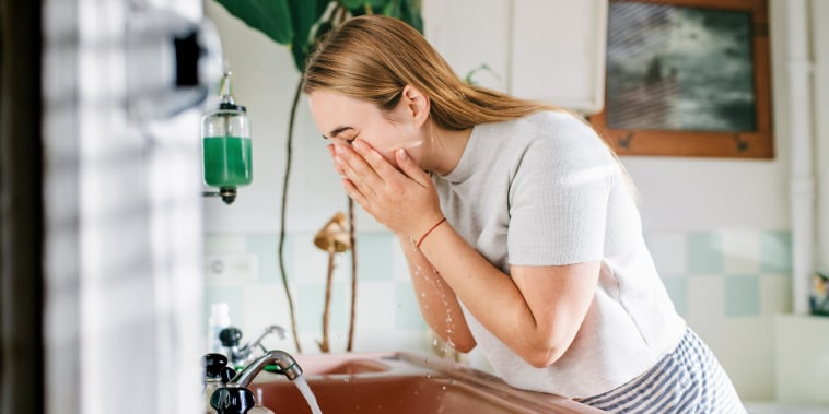 Woman washing her face, leaning over her sink, in the bathroom