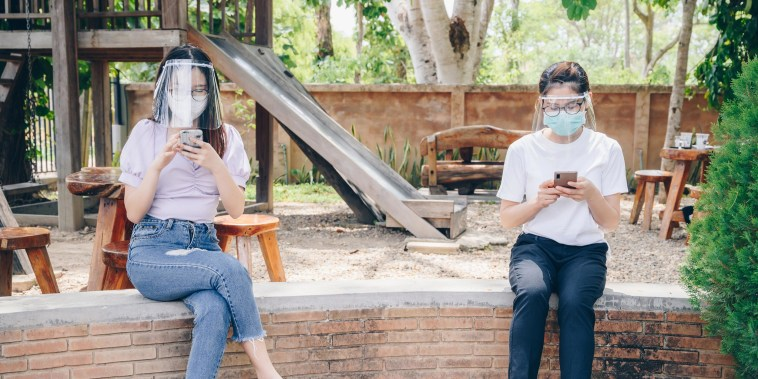 Two Girls 6 feet apart, sitting on a railing at the park wearing face masks and protective eye shields. Shop the best expert-recommended coronavirus eye protection to wear during the pandemic like glasses, goggles and face shields.