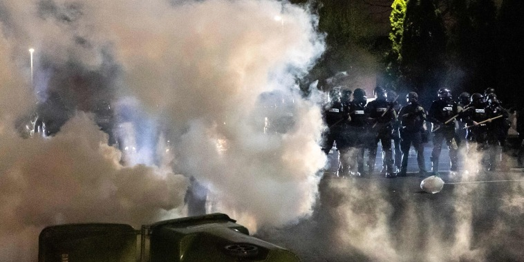Image: Police officers in riot gear fire tear gas in front of the Brooklyn Center Police Station as people gather to protest after a police officer shot and killed a black man in Brooklyn Center, Minneapolis,