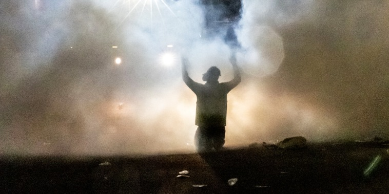 A person kneels and holds up his arms as police fire tear gas in front of the Brooklyn Center Police Station during a protest after a police officer shot and killed a black man in Brooklyn Center, Minneapolis, on April 11, 2021.