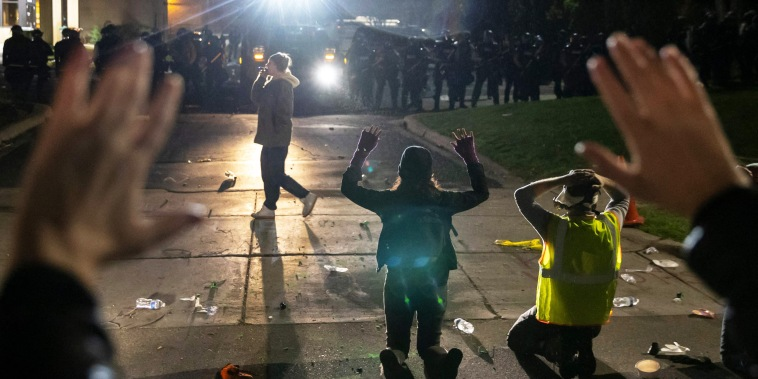 "Protestors shout ""Don't shoot\"" while kneeling and raising up their arms in front of a line of police officers at the Brooklyn Center Police Station during a protest after a police officer shot and killed a Black man in Minneapolis on April 11, 2021."