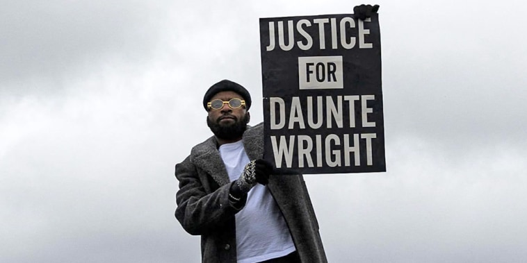 Image: People gather holding signs and flags before curfew to protest the death of Daunte Wrigh