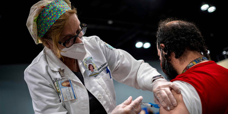 Image: Dr. Susana Schwarz inoculates a man with the Johnson and Johnson Covid-19 vaccine at the Puerto Rico Convention Center during the first mass vaccination event in San Juan, Puerto Rico