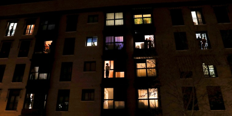 Image: People look out of their apartment windows to show gratitude to healthcare workers during the coronavirus outbreak in Madrid on March 14, 2020.
