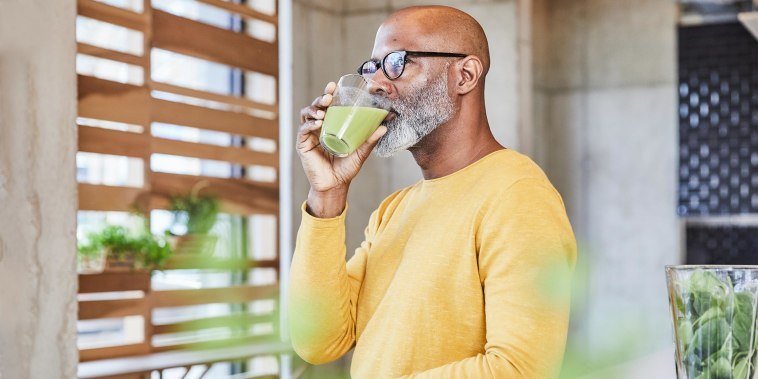 Man leaning on a counter drinking green juice