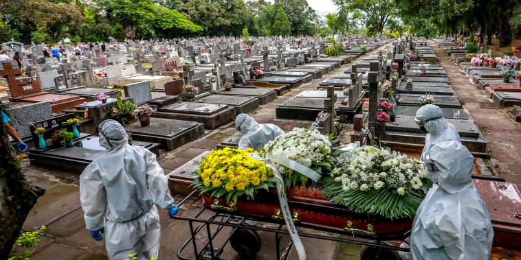 Image: Cemetery workers carry a coffin during the burial of a victim of Covid-19 at the Sao Joao municipal cemetery in Porto Alegre, Brazil, on March 26, 2021.